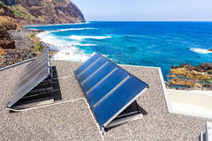 Blue solar panels on roof at sea Stock Photography