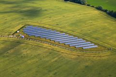 Blue solar panels surrounded by beautiful green fields - bird eye perspective stock image