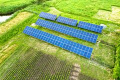 Free Blue Solar Photo Voltaic Panels Mounted On Metal Frame Standing On Ground With Green Grass In Field Stock Photos - 173198363