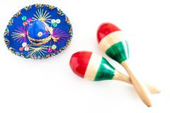Blue sombrero with colorful ornaments on white background next to colorful maracas. Symbol of Mexico concept.  royalty free stock photo