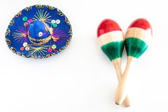 Blue sombrero with colorful ornaments on white background next to colorful maracas. Symbol of Mexico concept.  stock photography