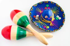 Blue sombrero with colorful ornaments on white background next to colorful maracas. Symbol of Mexico concept.  stock photo