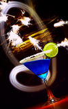 Blue and sparks. View of cocktail glass with a piece of lime   in fireworks light Stock Photos
