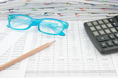 Blue spectacles brown pencil and calculator on finance account. Blue spectacles, brown pencil and calculator on finance account with pile of paperwork as Royalty Free Stock Photo