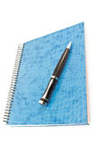 Blue spiral notebook with pen Stock Photography