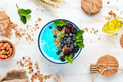 Free Blue Spirulina And Fresh Fruit Smoothie Bowl Topped With Blackberries, Blueberries, Granola And Yogurt. Breakfast. Stock Images - 164636584