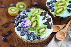 Blue Spirulina and Berry Smoothie Bowl with Blueberries Chocolate and Kiwi royalty free stock photo