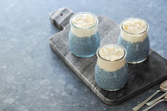 Blue Spirulina Chia Pudding with Coconut Cream. Three raw vegan chia puddings topped with whipped coconut cream on a stone board. These puddings are made blue Royalty Free Stock Image
