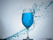 Blue splash colision. Another splashing with glass of wine Stock Image