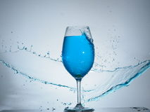 Blue splash colision. Another splashing with glass of wine Royalty Free Stock Images