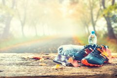 Blue sport shoes and water laid on a wooden board. Pair of blue sport shoes smart phone and water laid on a wooden board in a tree autumn alley with maple stock photos