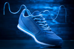 Blue sport sneakers on a wooden background Stock Photos
