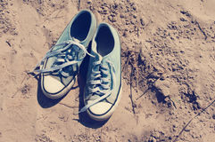 Blue sports gym shoes on sand. Couple of blue sports Siberian salmons with white laces on sand Stock Photos