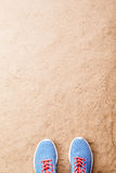 Blue sports shoes laid on sand beach, studio shot Royalty Free Stock Photo