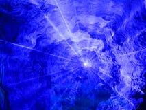 Blue spotlight shining through smoke Stock Image