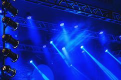 Blue spotlights of a stage with light cannons, led lights, steel. Structure and fog ambience. Music show or presentation background Royalty Free Stock Images