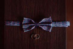 Blue spotted bow tie lies before golden wedding rings.  Stock Image