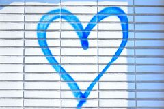 Blue spray-painted hart. Vandalism on a white wall stock photos