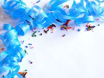 Blue Sprinkles and Spirals. Blue curling ribbon and candy sprinkles party theme with blank space to add your own text Royalty Free Stock Image