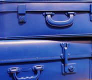 Blue stacked vintage style suitcases. Blue stacked vintage retro style suitcases with click fasten lock Royalty Free Stock Image
