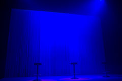 Blue stage spotlights with three stools Stock Images