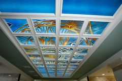 Blue stained glass on the ceiling in a white frame with colorful hand-painted patterns. royalty free stock image