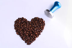 Blue stainless steel coffee temper with roasted coffee beans in Royalty Free Stock Photography