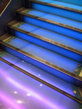 Blue Staircase. A staircase made from transparent Perspex. Blue and purple lights glow from below royalty free stock photo
