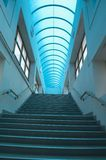 Blue staircase vertical. Interior of a modern building with ascending staircase and blue transparent roof. Vertical composition Royalty Free Stock Photo