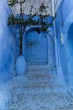 Blue stairs and door. Traditional blue stairs and door with shadow, Chefchaouen, Morocco Stock Photo