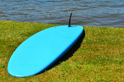 Blue standup paddle board on river bank Stock Image