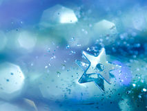 Blue star background. A tiny star with bokeh glitter and a blue background Stock Photos