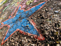 Blue star. Painted star with dead leaves Royalty Free Stock Image