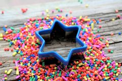 Blue star and party decoration. Colorful confetti, wooden background and text space Royalty Free Stock Photo
