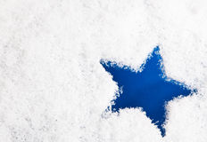 Blue star on snowy background Stock Photos