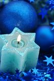 Blue Starcandle. Holiday Candle with christmas decoration Royalty Free Stock Photo