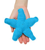 Blue starfish. Hand made toy - blue starfish in female hand. Isolation Royalty Free Stock Image