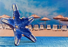 Blue starfish shape against parasols on beach Stock Photos