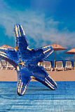 Blue starfish shape against parasols on beach Royalty Free Stock Image