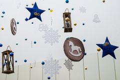 Festive decoration of the room in the New Year`s style. Blue stars, snowflakes, lanterns, horses, bells and other toys hang on. Blue stars, snowflakes, lanterns royalty free stock image