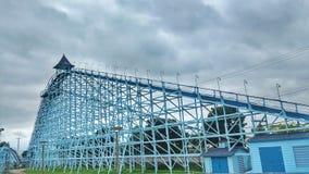 Vintage wooden roller coaster incline track at amusement park. The Blue Steak Roller coaster at Cedar Park, Sandusky Ohio against dramatic skies Stock Image