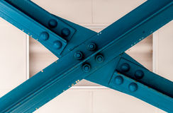 Blue steal beam. Blue construction beam forming an X. Halogen light background, industrial construction. Painted steel beams. Minimal industrial modern art Royalty Free Stock Images