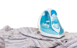 Blue steam iron and shirt on white background. Royalty Free Stock Photo