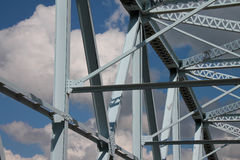 Blue Steel Bridge Left View. Left view of old light blue steel frame bridge with cloudy sky overhead Stock Image
