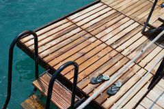 Blue step-ins on the wooden sea pier stairs Stock Photography