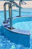 Blue steps that descend towards the big blue resort pool. Ceramic steps that descend towards the big blue resort pool Royalty Free Stock Photography