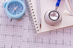 Blue stethoscope,alarm colck,notebook and cardiogram pulse trace. Concept for cardiovascular medical exam. Medical and health concept Stock Photography