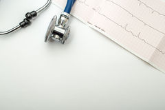 Blue stethoscope and cardiogram lie on a table Royalty Free Stock Photo