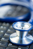 Blue stethoscope in the middle of keyboard Stock Images