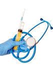Blue stethoscope and yellow syringe Stock Image